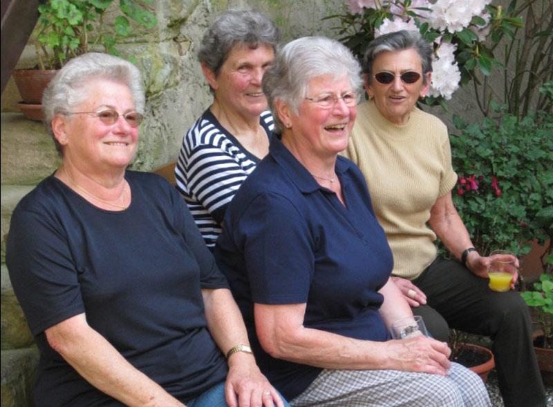 Vier Seniorinnen sitzen auf einem Bänkle